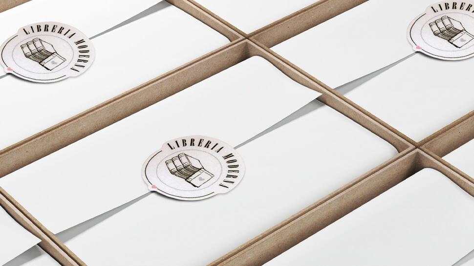Etichette chiudipacco adesive personalizzate su confezione di cartoleria di pregio chiara